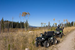 Hunting a logging clear cut. One hunter and two ATVs parked on the side of a dirt road that runs next to a logged forest. Clear blue sky over a grassy field Royalty Free Stock Images