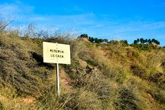 Hunting reserve signal in Spain. Sunny day. Leaky and rusty metal plate. Scrub and bushes stock images