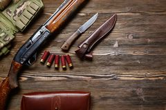 Hunting rifle and ammunition on a wooden background. Hunting rifle and ammunition on a dark wooden background.Top view Royalty Free Stock Images