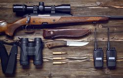 Hunting rifle and ammunition on a wooden background. Hunting rifle and ammunition on a dark wooden background.Top view Stock Photos