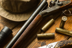 Hunting rifle, ammunition, a knife and a cap on the table Stock Images
