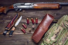 Hunting rifle and ammunition on a wooden background. Hunting rifle and ammunition on a dark wooden background.Top view Royalty Free Stock Photos