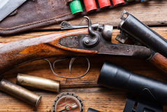 The hunting rifle, cartridge belt,binoculars on a wooden table. The hunting rifle, cartridge belt,binoculars,ammunition on a wooden table Stock Images