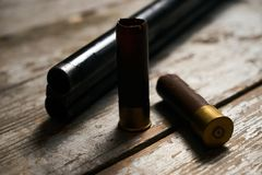 Hunting rifle with cartridges. Lying on a wooden table. Guns with bullets close-up Stock Photos