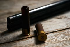 Hunting rifle with cartridges. Lying on a wooden table. Guns with bullets close-up Royalty Free Stock Photos