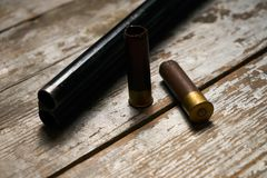 Hunting rifle with cartridges. Lying on a wooden table. Guns with bullets close-up Stock Image