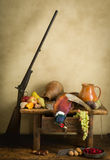 Hunting rifle and game. Wooden table with hunting rifle and dead pheasant Stock Photo