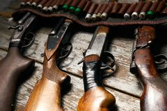 Hunting rifles with leather bandolier with ammunition. On wooden background. Different types of guns with cartridges, close-up Royalty Free Stock Photos