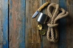 Hunting saver wallpaper. Brutal and sever background with a copy space. Rope, knife, compass and cup on a wooden table. Hunting saver wallpaper. Brutal and sever stock images