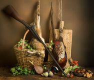 Hunting scene with basket. Autumn still life with hunting rifle, pheasant and hare Royalty Free Stock Image
