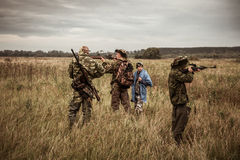 Hunting scene with hunters aiming during hunting season in rural field in overcast day with moody sky Royalty Free Stock Photography