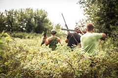 Hunting scene with hunters breakthrough thickets during hunting season in hot summer day Royalty Free Stock Images