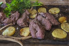 Hunting season meal: deer meat. Deer meat roasted with potatoes and decorated with deer antler and parsleay stock image