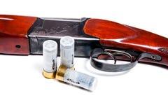 Hunting shotgun and ammunition on white background. Royalty Free Stock Photo