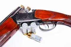 Hunting shotgun and ammunition on white background. Royalty Free Stock Image