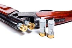 Hunting shotgun and ammunition on white background. Stock Images