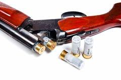 Hunting shotgun and ammunition on white background. Stock Photography
