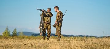 Hunting skills and weapon equipment. How turn hunting into hobby. Friendship of men hunters. Army forces. Camouflage. Military uniform fashion. Man hunters royalty free stock image