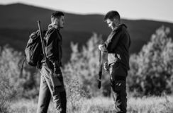 Hunting skills and weapon equipment. How turn hunting into hobby. Friendship of men hunters. Army forces. Camouflage. Military uniform. Man hunters with rifle royalty free stock photo