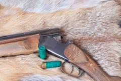 Hunting smooth-bore gun. Lies on Fox skin stock photography