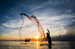 Hunting for Sunset. Silhouette of unidentified fisherman casting fishing net. stock images