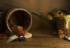 Hunting table and rifle. Hunting still life with pheasant, basket and fruit Stock Photos