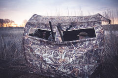 Hunting tent with hunters waiting for prey in reed bushes Stock Photography