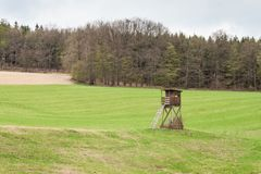 Hunting Tower on a field near the forest. Hunting deer. Overcast day. Stock Photos