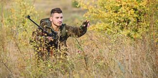 Hunting and trapping seasons. Bearded serious hunter spend leisure hunting. Man wear camouflage clothes nature. Background. Hunting permit. Hunter hold rifle royalty free stock photography