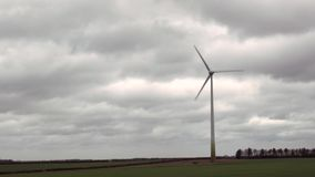 Wind turbines spin on background of dark clouds stock footage