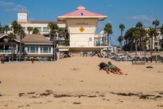 Two people laying on the sand, in the sun in front of a lifeguard stand with their hats over their faces. Huntington Beach, California - October 11, 2018: Two royalty free stock photos