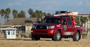 Huntington Beach Lifeguard Patrol. Huntington Beach lifegaurd patroling beach in red truck with surfboard Royalty Free Stock Images