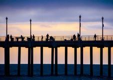 Huntington Beach Pier at Dusk Against a Sunset. A slice of Huntington Beach Pier and strollers in silhouette against an orange and purple dusk sky with lamp royalty free stock photos