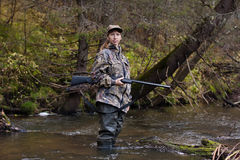 Huntress with gun on the river. Woman hunter in camouflage with gun on the river Stock Photos