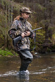 Huntress with gun. Woman hunter in camouflage with gun crossing the river Stock Photos