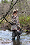 Huntress with stuffed duck. Woman hunter in camouflage with gun and stuffed duck on the river Royalty Free Stock Image