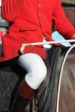Fox hunt Huntsman ready horse whip jacket. Fox hunt Huntsman on horses England Tradition red jacket whip and horse Stock Image