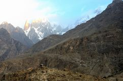 Snow capped mountains in Hunza Valley at sunrise Gilgit-Baltistan Pakistan. Hunza, Pakistan - September 30, 2016: Snow capped mountains at sunrise in Pakistan`s royalty free stock photo