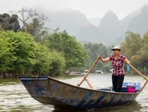 Vietnamese woman rowing a boat on the way to Perfume Pagoda, a popular day trip from Hanoi. Huong Son, Vietnam - March 8, 2016: Local woman rowing a boat on the Stock Images
