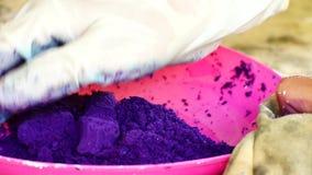 Hur man gör kulört pulver holifestival Händerna saltar matfärgläggning som är blandad med havrestärkelse för att göra en mjölcolo arkivfilmer