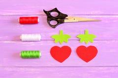 Hur man räcker sy barn leksakjordgubben moment tutorial Delsnitt från röd och grön filt i formen av jordgubbar Arkivfoto