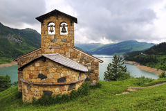 Сhurch on the mountain lake shore. French Alps: сhurch on the mountain lake shore Stock Photos