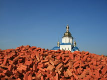 Hurch over red bricks pile 3. Renewed orthodox church over red bricks pile against deep blue sky Royalty Free Stock Images