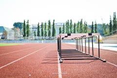 Hurdle race on stadium track Stock Photography