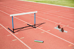 Hurdle, relay baton and a starting block kept on a running track Royalty Free Stock Image
