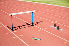 Hurdle, relay baton and a starting block kept on a running track Royalty Free Stock Images