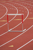 Hurdle track lane. A red and white hurdle in a lane, on a synthetic track stock photos