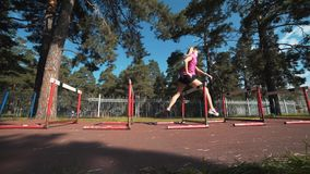 Hurdler femenino profesional en la acción Corriendo con los obstáculos, entrenando metrajes