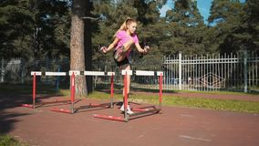 Hurdler femenino profesional en la acción Corriendo con los obstáculos, entrenando almacen de metraje de vídeo