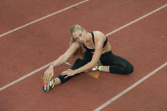 Hurdler's stretch in the running lane Stock Photo